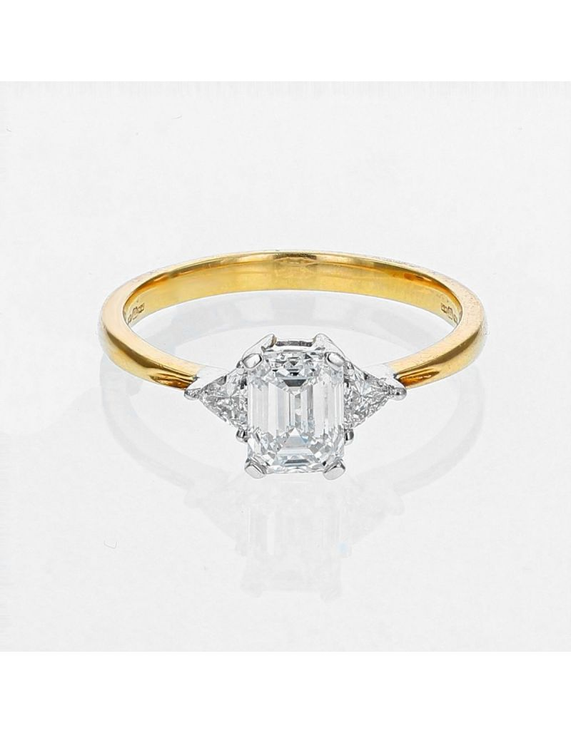 The Olivia Collection Emerald Center Stone 0.96 Carat With Two Trillion Cut Diamonds On The Side AGI Certificated Diamond Ring Set In 18 An Carat Yellow Gold Shank